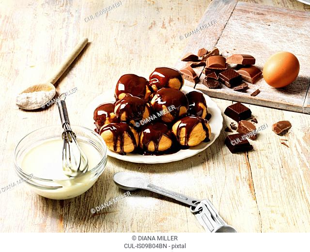 Profiteroles with hot chocolate sauce, cream filling in bowl with whisk, wooden spoon with flour, egg, sugar in measuring spoon, pieces of chocolate