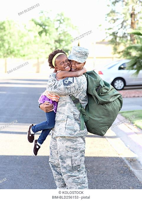 Black woman soldier hugging daughter in street