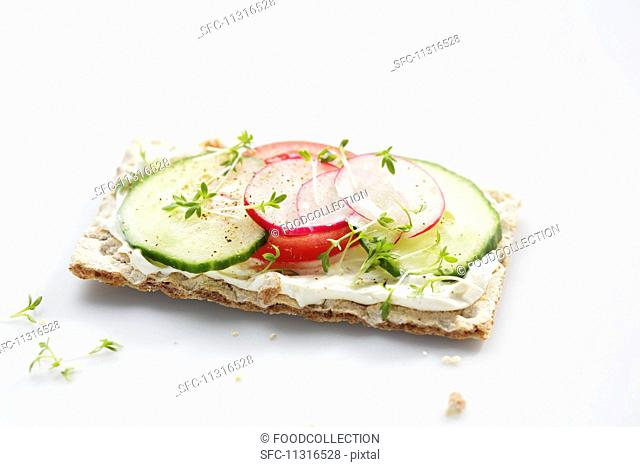 A crispbread topped with cucumber, tomato, radishes and cress