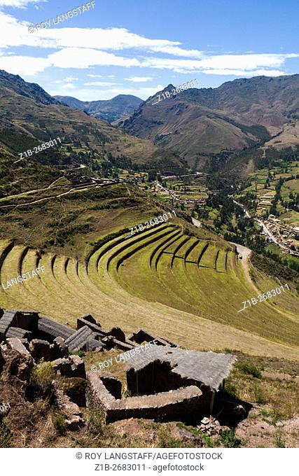 View of the Incan agricultural terraces at Pisac with protective roofing over the stone ruins in the foreground