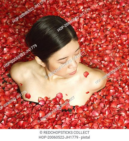 High angle view of a young woman in a bath tub full of rose petals