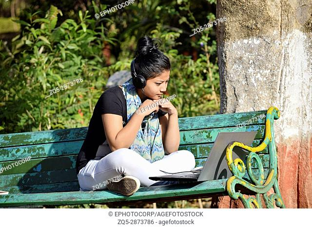 Young girl student studying outside in the garden with laptop and headphone, Pune, Maharashtra