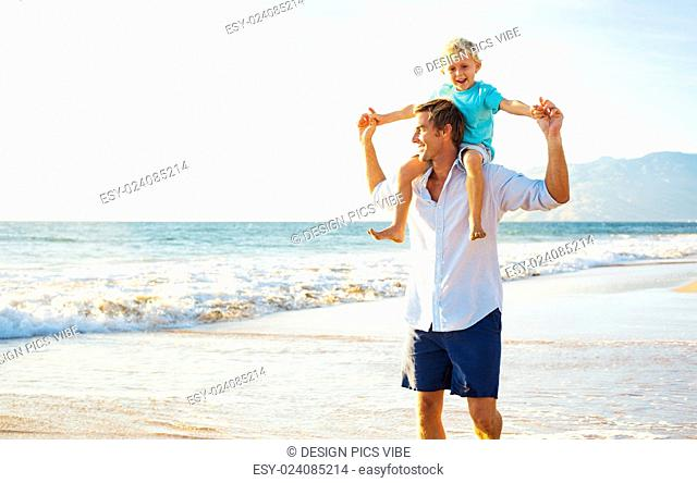 Father and Son Playing and Walking on the Beach at Sunset