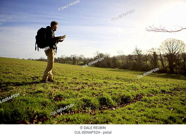 Male hiker walking in field whilst reading folding map