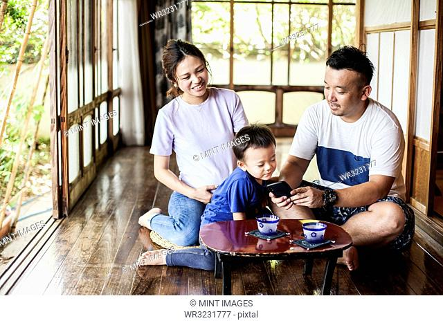 Japanese woman, man and little boy sitting on floor on porch of traditional Japanese house, drinking tea