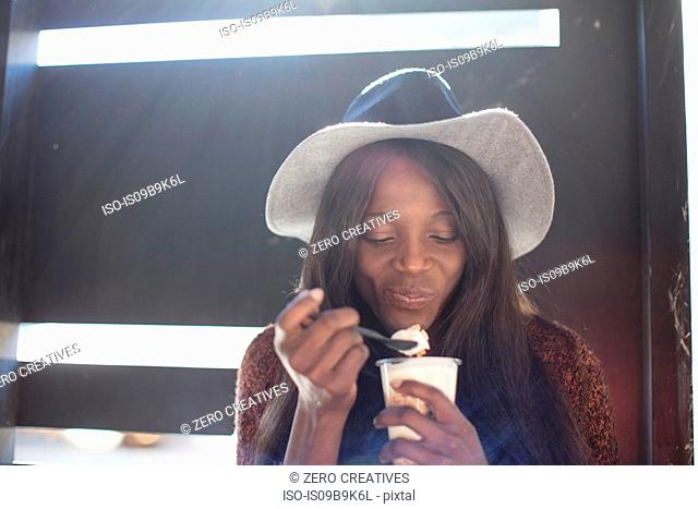 Young woman, eating dessert with spoon