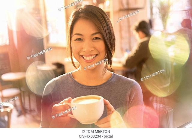 Portrait smiling woman drinking cappuccino in cafe