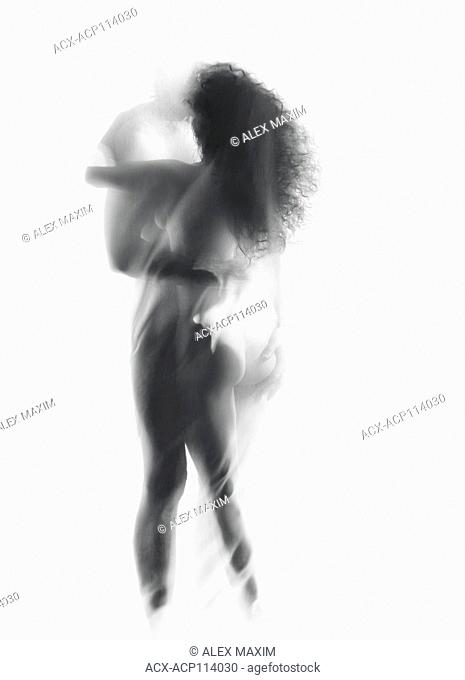 Artistic surreal portrait of a sexy nude couple, embracing man and a woman, kissing behind a veil of a glowing sheer white curtain