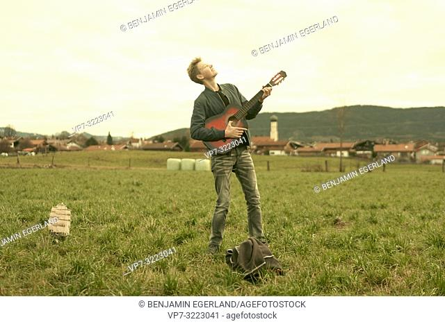 male teenager with guitar standing on meadow outdoors at countryside, in Waakirchen, Bavaria, Germany