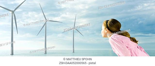 Ecology concept, girl blowing on blades of wind turbines