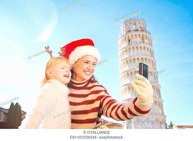 Happy mother in Christmas hat and daughter wearing funny reindeer antlers taking selfies in front of Leaning Tour of Pisa, Italy