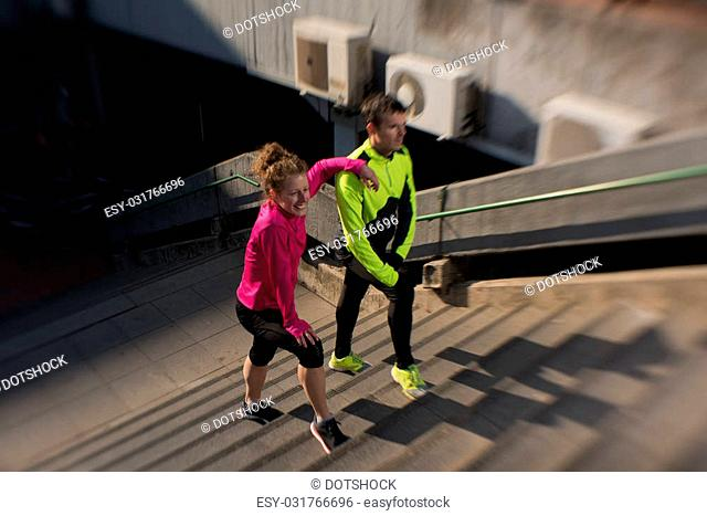 healthy young couple jogging on steps at early morning