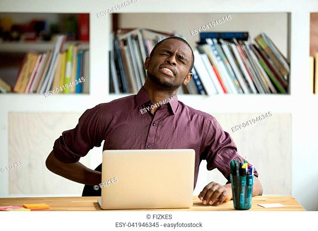 African-american man touching back sitting at desk feeling sudden backache, black businessman suffering from low-back lumbar pain after sedentary work at laptop...