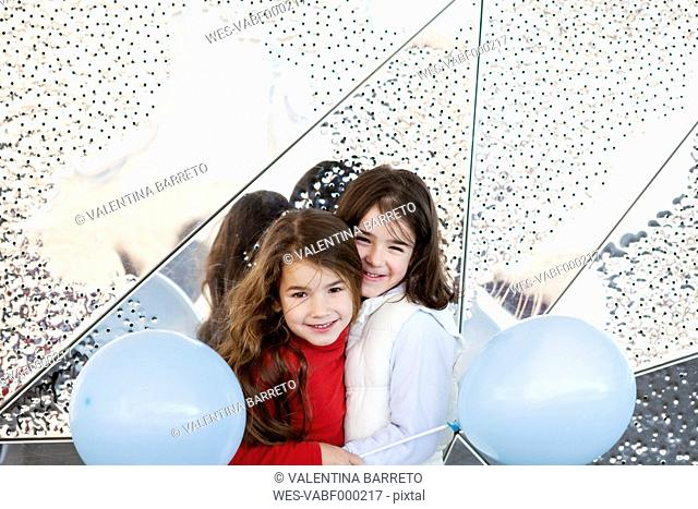 Two little girls with balloons cuddling in front of metal wall