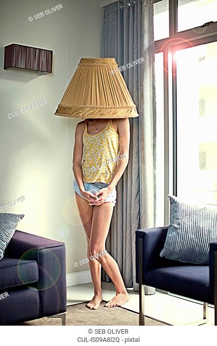 Young woman wearing lampshade on head