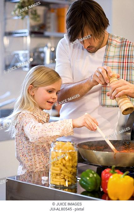Young girl helping father cook on stove