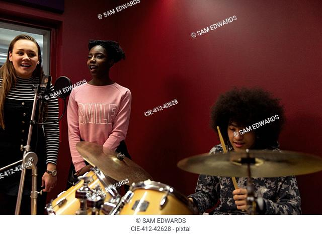 Teenage musicians recording music, singing and playing drums in sound booth