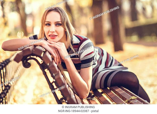 Pensive young blonde woman sitting on a bench in the street of a park with autumn colors. Beautiful girl in urban background wearing striped dress and black...