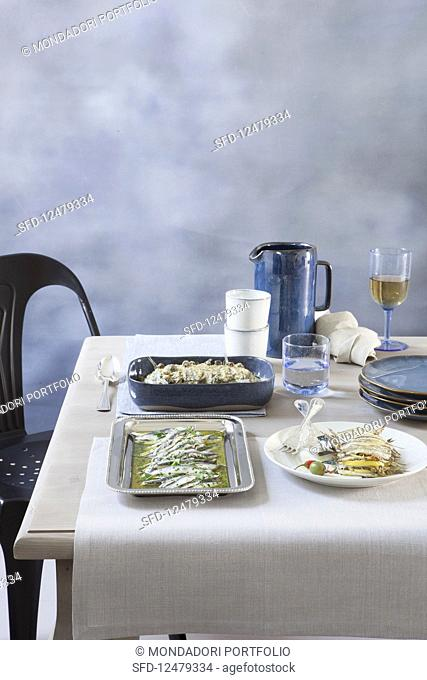 Various sardine dishes on a laid table