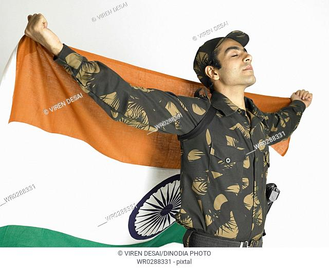 Indian army soldier standing holding flag of India on his backside MR702A