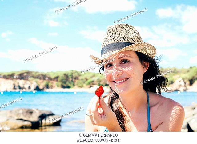 Portrait of smiling woman wearing straw hat on the beach holding strawberry