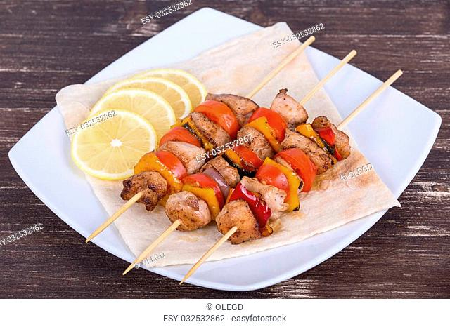 Grilled meat and vegetables on skewer in the plate