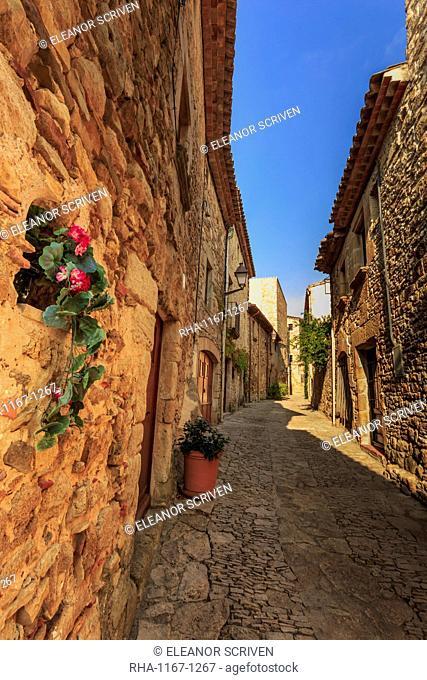 Gorgeous medieval village, cobblestone narrow lane and flowers, Peratallada, Baix Emporda, Girona, Catalonia, Spain, Europe