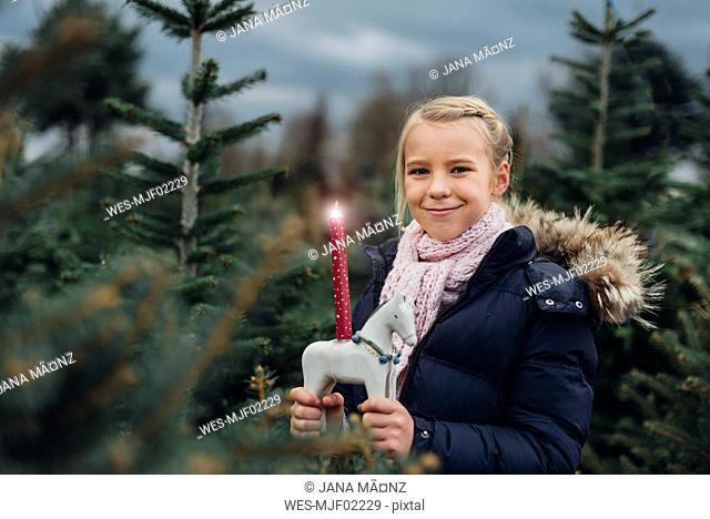 Little girl standing in front of fir trees with a burning candle