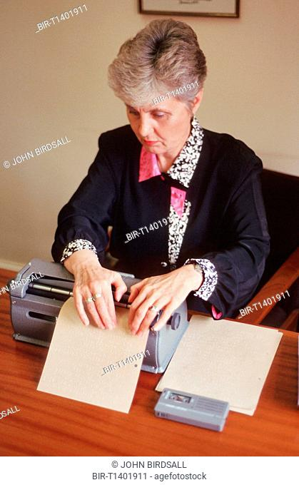 Woman with visual impairment sitting at desk using Braille typewriter