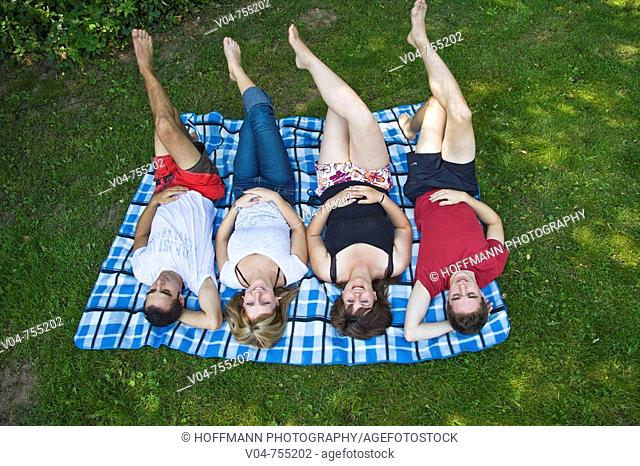 Four young people lying on a blanket in the garden, smiling