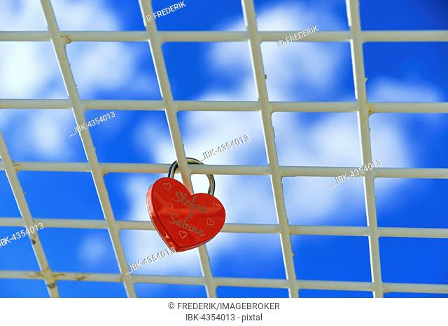 Red padlock, heart shaped, love lock on grid in frint of blue sky, Lower Saxony, Germany