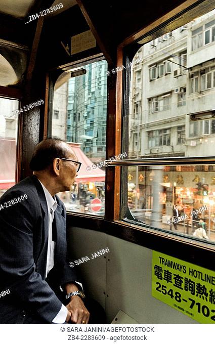 Local man looking from window of a doble deck tramway, Hong Kong Island, Hong Kong, China, East Asia