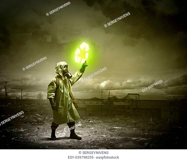 Image of man in gas mask and protective uniform touching recycle sign