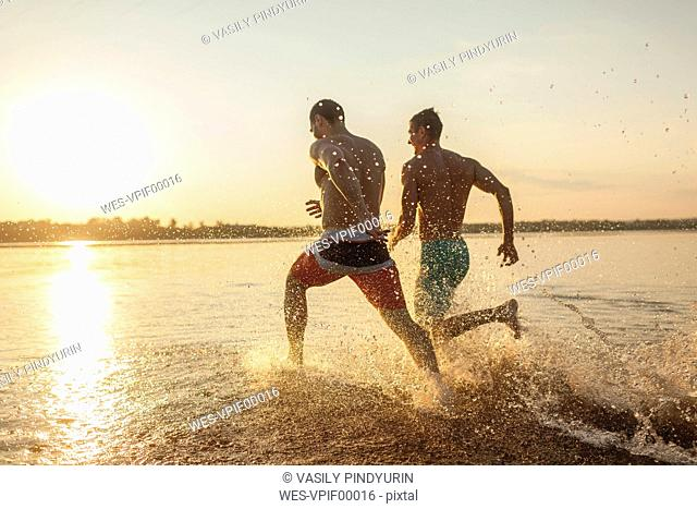 Two friends running in water