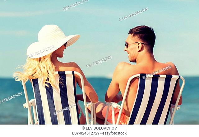 love, travel, tourism, summer and people concept - smiling couple on vacation in swimwear sitting in chairs and sunbathing on beach from back