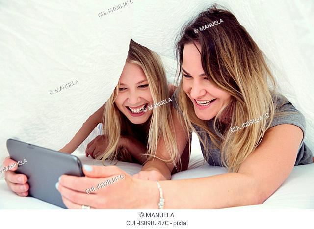 Friends underneath bed sheet using digital tablet smiling