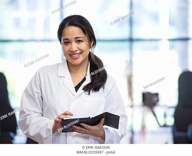 Portrait of smiling Asian physical therapist using digital tablet