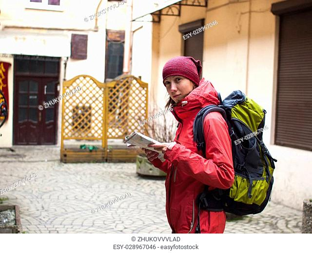 A lonely girl with a backpack and a map of the walks around the old town