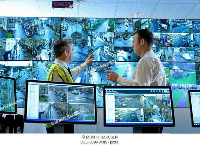 Security guards in discussion in security control room with video wall