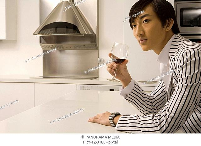 Man sitting at table in kitchen and holding wineglass