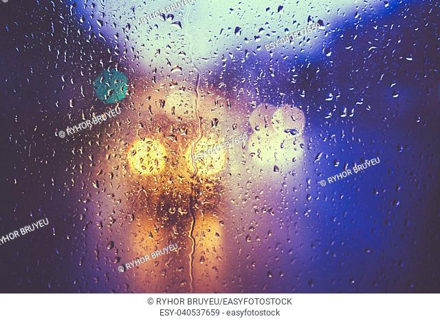 Drops Of Rain On Blue Glass Background. Street Bokeh Lights Out Of Focus. Autumn abstract backdrop. Toned like instant photo