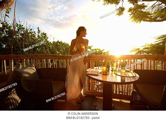 Pacific Islander woman admiring sunrise from patio