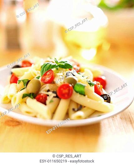 eating penne pasta salad with fork