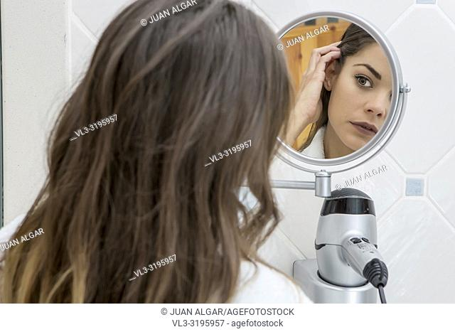 Back view of young brunette exploring tender skin in small mirror inside of bathroom
