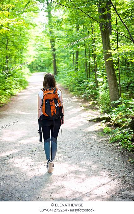 Young woman hiker with backpack walking on hiking trail in sunny summer forest. Hilton Falls conservation area, Ontario, Canada