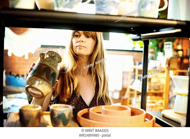 Woman standing in a shop, holding a small ceramic vase