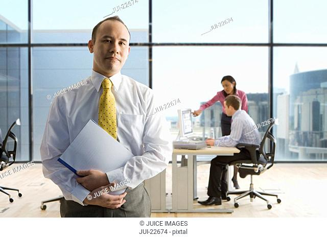 Businessman holding file with co-workers working in background