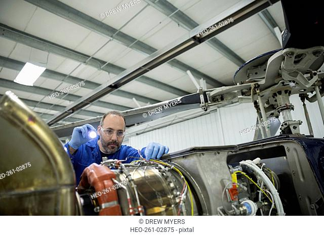 Helicopter mechanic working on part with flashlight