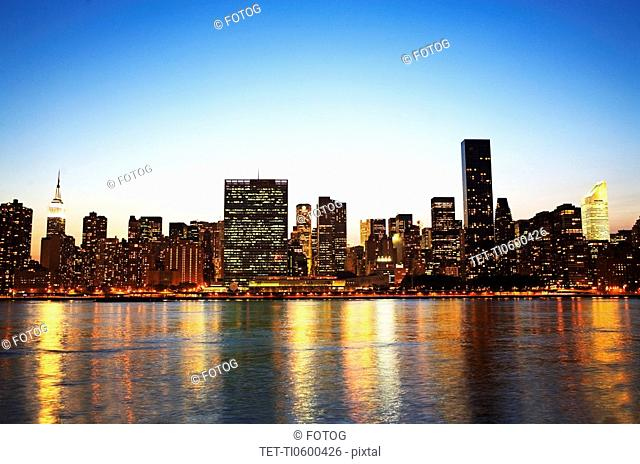 New York City skyline along water at night