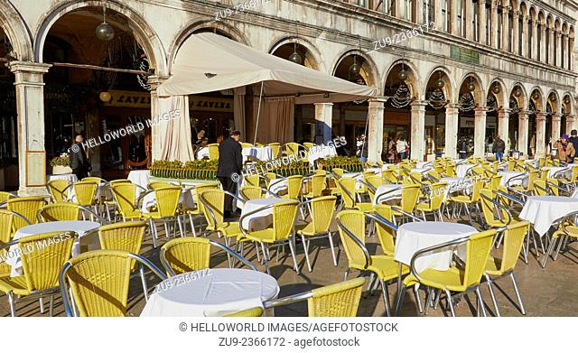 Alfresco cafe tables and chairs in winter sun alongside elegant arched colonnade, Piazza San Marco, Venice, Veneto, Italy, Europe